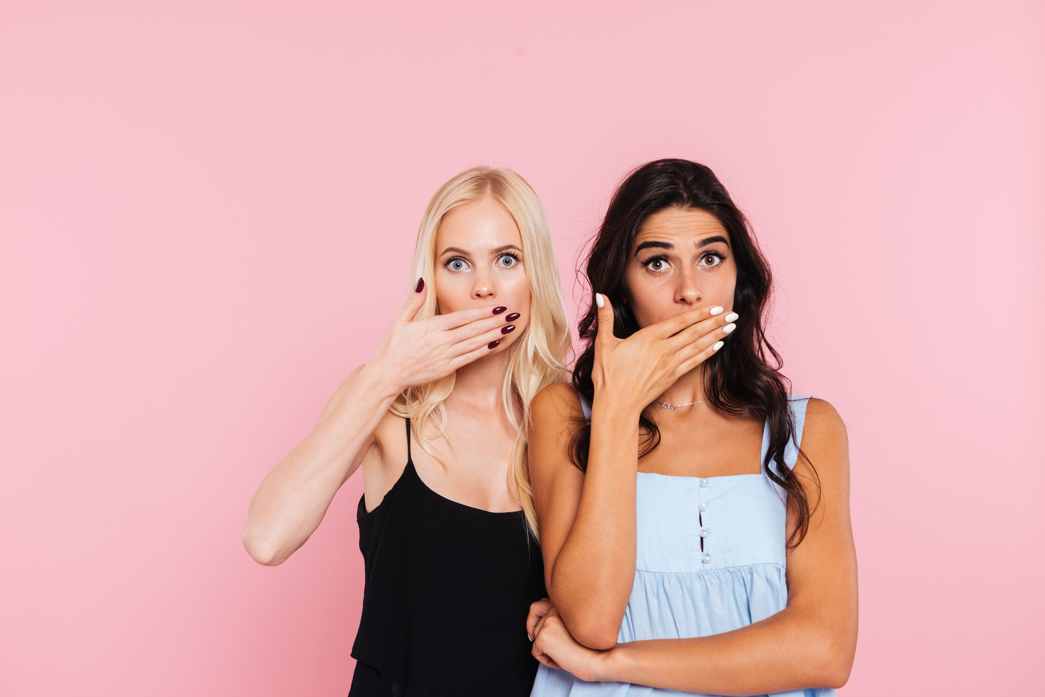 Two surprised women covering her mouths