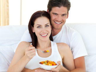 Happy couple eating fruits lying on their bed at home