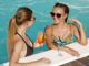 Young beautiful female friends chatting while having drinks together at the swimming pool.