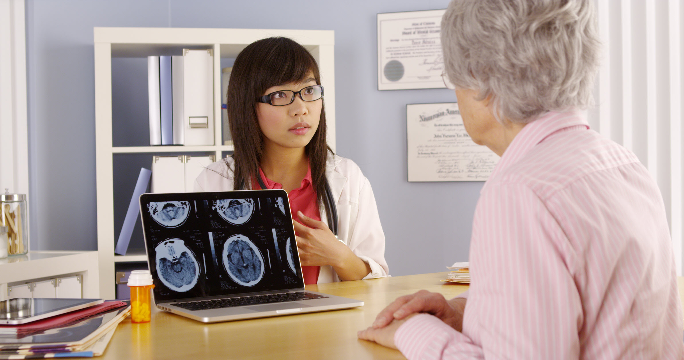 Asian doctor explaining brain scans to elderly patient.
