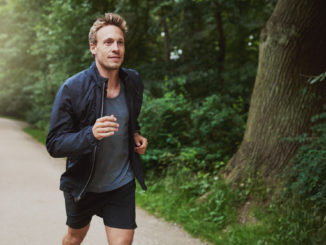 Three Quarter Shot of a Healthy Young Man in Jacket Shirt, Jogging at the Park Early in the Morning.
