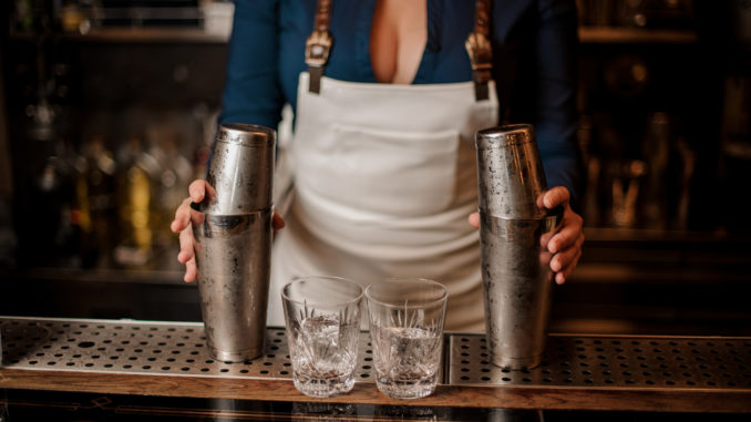 Female bartender in the white apron holding in her hands two steel cocktail shakers standing at the bar counter