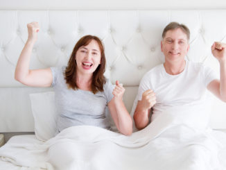 Happy smiling middle age couple in bed in t shirt