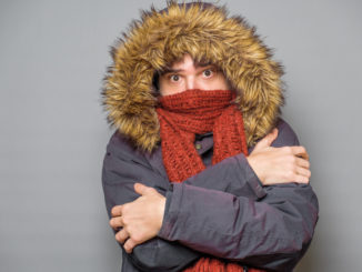 Studio portrait of man feeling cold and wearing warm clothes