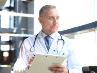 Portrait of focused senior doctor writing reports.