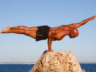Balance strong man balancing on rock.