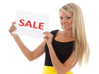 Young beautiful woman with sale sign on a white background.