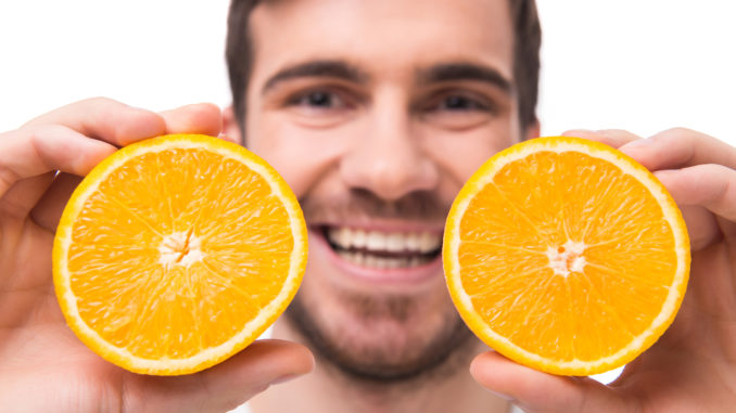 Young man is holding oranges in front of his eyes. Close-up.