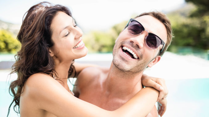 Young couple cuddling each other near pool at sunny day