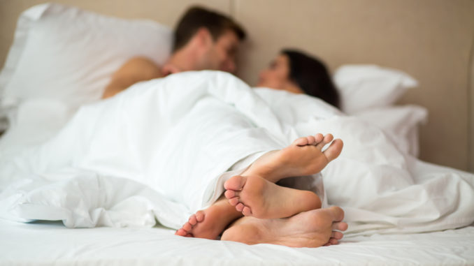 Couple`s feet in bed. Man with women under blanket. Rest in home comfort.