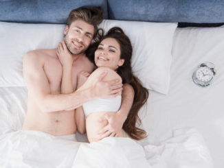 Top view of beautiful happy couple in bed looking at camera