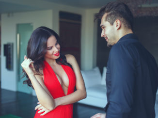 Woman in red dress and lis flirting with young men indoors, playing with hair