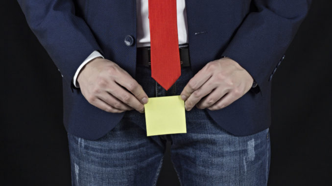 man holding sticker in his groin area, black background