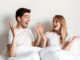 Image of young happy excited loving couple lies in bed looking at each other with mouth opened.