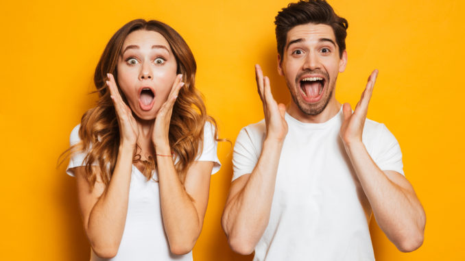 Photo of excited couple men and women in basic clothing shouting in surprise or delight and raising arms isolated over yellow background