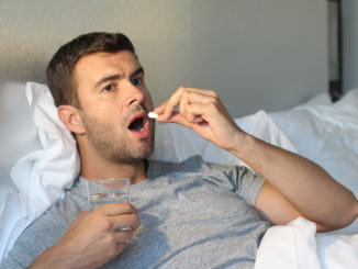 man taking medicine in bed.