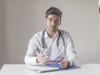 Frontal view of a young doctor talking to the camera.