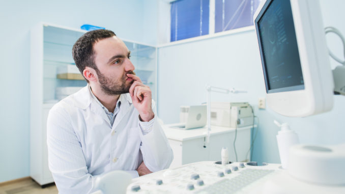 Portrait of a thinking doctor near sceen of medical equipment