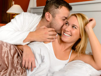 Happy couple in bed men giving kiss women cheek