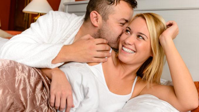Happy couple in bed men giving kiss women cheek