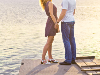 Happy couple hugging while standing on the bank of a river on summer