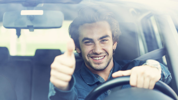 Young man thumbs up gesture in the car