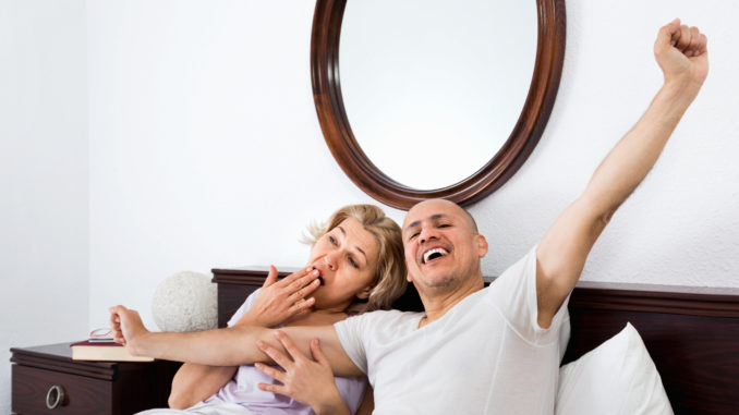 Positive cheerful mature loving couple lounging in bed after awaking cuddling