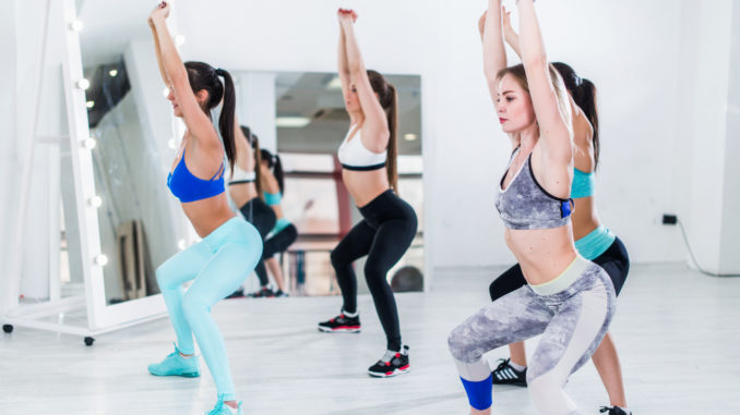 Young slender women doing overhead squat exercise during group training in gym.