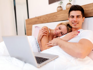 Happy couple in bed using notebook and smiling