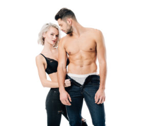 seductive women looking at camera and unzipping pants of muscular men on white