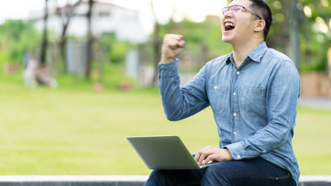 Attractive asian happy man gesture or raise hand excited screaming yes reading online