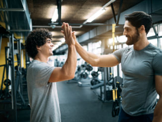 Fit men high fiving at the gym