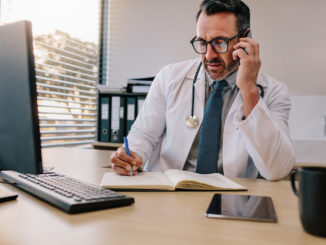 Medicine professional talking on phone and writing in his diary