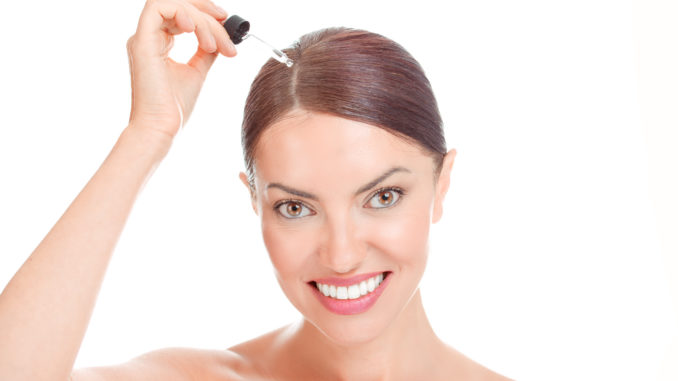 Woman applying serum essence essential oils to her hairline for growth