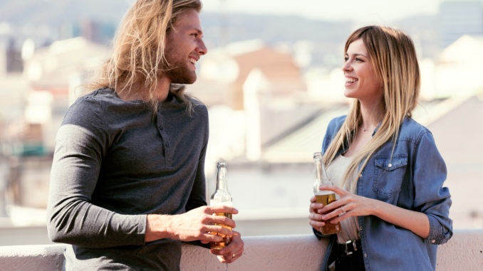 Shot of pretty young couple talking while drinking beer on the rooftop at home