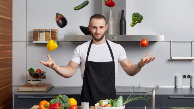 Young man in the kitchen juggling with vegetables
