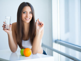 Beautiful Smiling Woman Taking Vitamin Pill and Dietary Supplement.