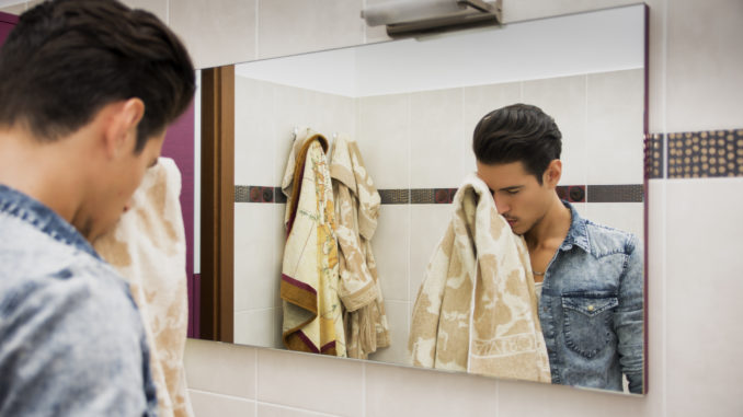 Reflection of Young Man Drying Face with Towel in Mirror as Part of Daily Hygiene Routine