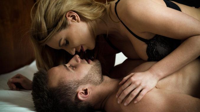 Woman seducing men lying on him in lingerie