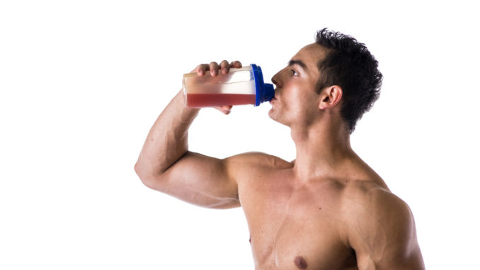Muscular shirtless male bodybuilder drinking protein shake from blender. Isolated on white, looking to a side, profile view.