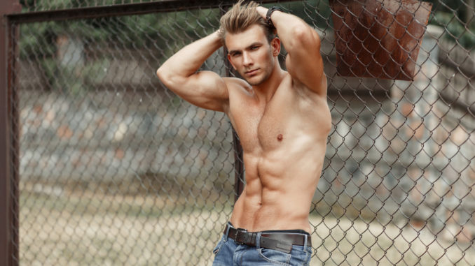 Fitness model man with a beautiful healthy body with muscles posing near a metal grid