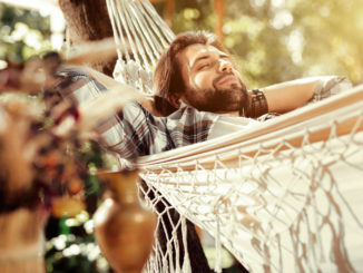 So comfortable. Nice happy man smiling while sleeping in the hammock