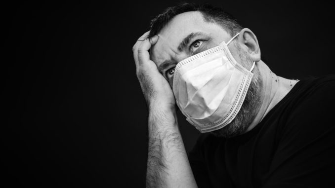 Black and white portrait of sick man in medical mask on dark background with copyspace