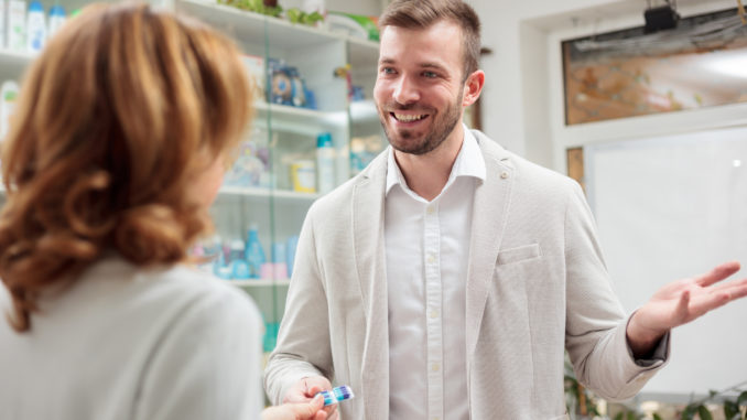Handsome young men wearing casual business suit buying pills in a pharmacy,