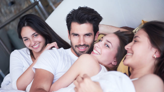 Young macho playboy handsome men in bed with three beautiful woman