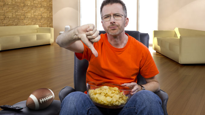 man watching football on TV with potato chip snacks