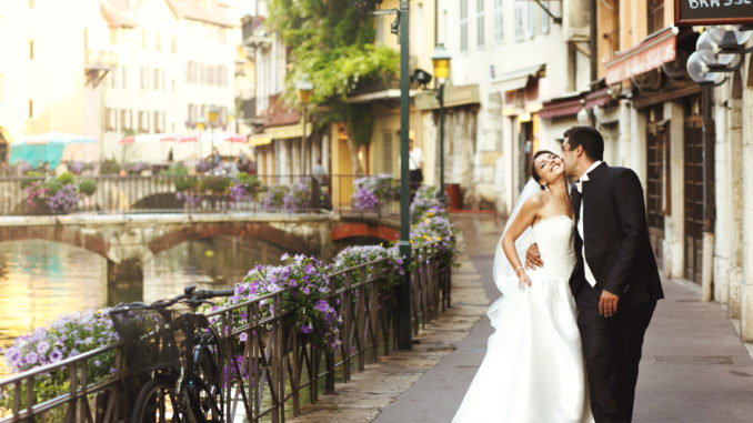 Happy married couple bride and groom kissing & hugging in old french street