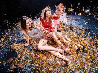 Three stylish young women sitting on the floor covered with confetti