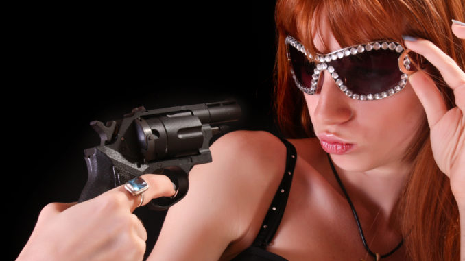Young redhead woman and gun to her face on black background