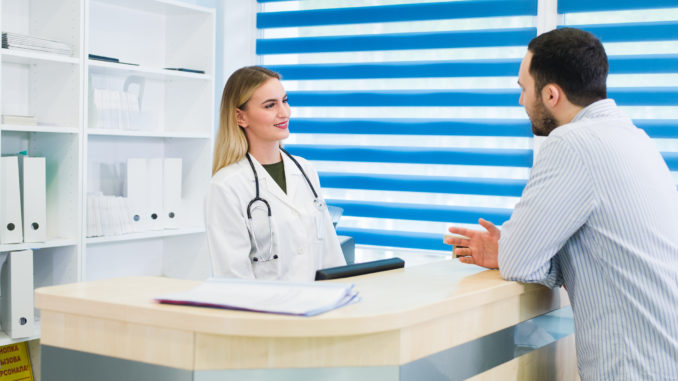 Man talking to female receptionist at hospital.